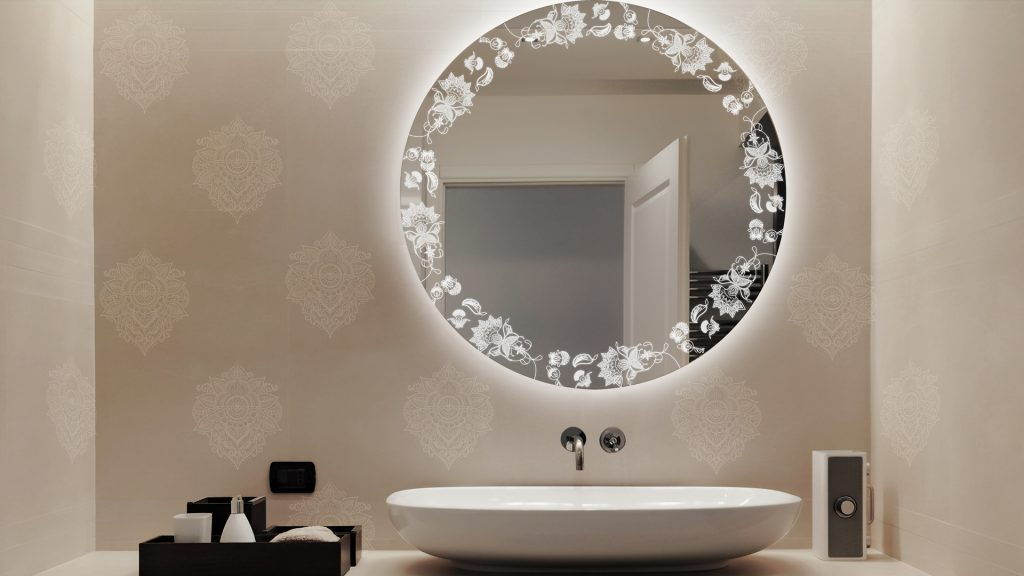 Round Lighted Etch Mirror in Paisley Design above a single sink mirror