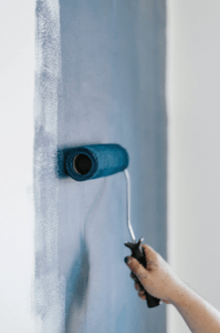 A wall being painted blue by a hand for a bathroom renovation project